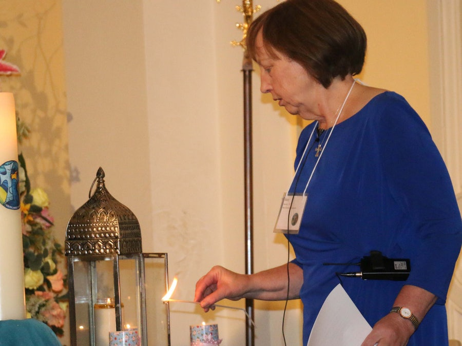 Mary Reynolds rsm lighting the three candles representing the 3 prayer intentions