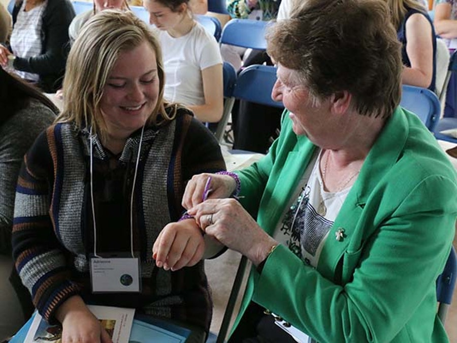 Adrienne Kelly and Mary Murphy rsm (The Congregation/ South Central) tieing on the wrist bands during the Opening Process