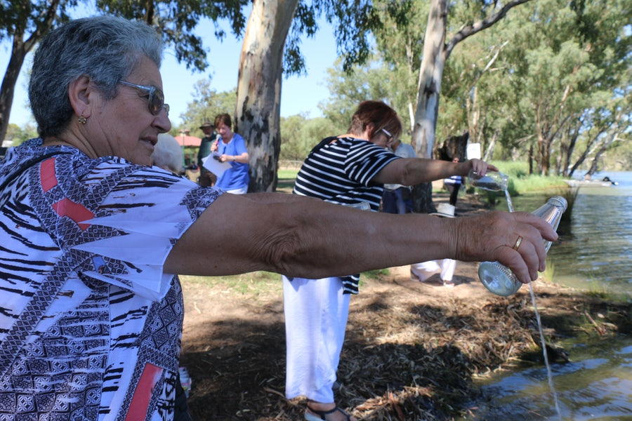 Christine Coughlan rsm (on right) begins the pouring of the water with a local citizen . Adele Howard rsm MC (background) invites those with water to come forwardto participate in this symbolic action
