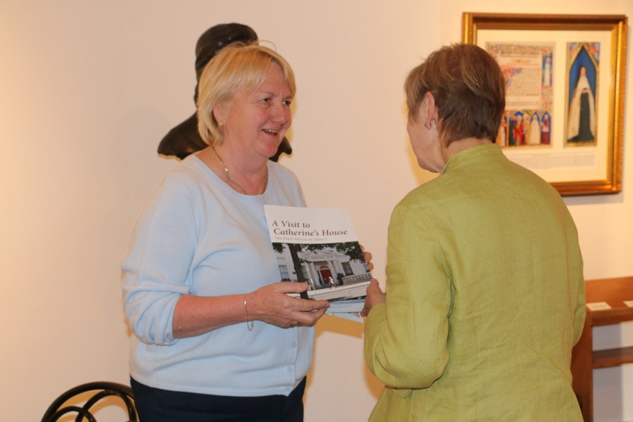 Anne Walsh showing Lorraine Nicholls (volunteer) 'A Visit to catherine's House' guide booklet, 2017