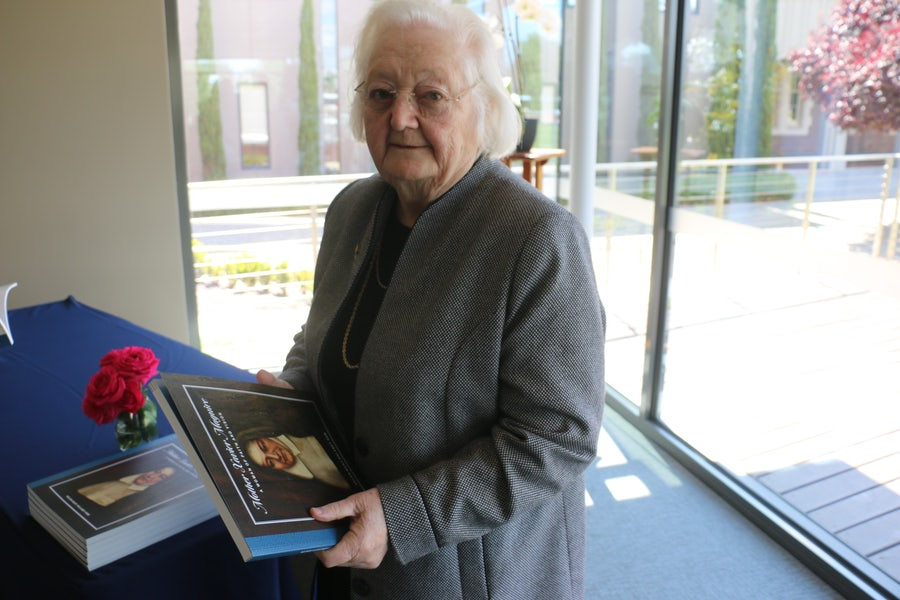 Helen Delaney rsm with a copy of her book on Xavier Maguire. The roses are Maguire roses