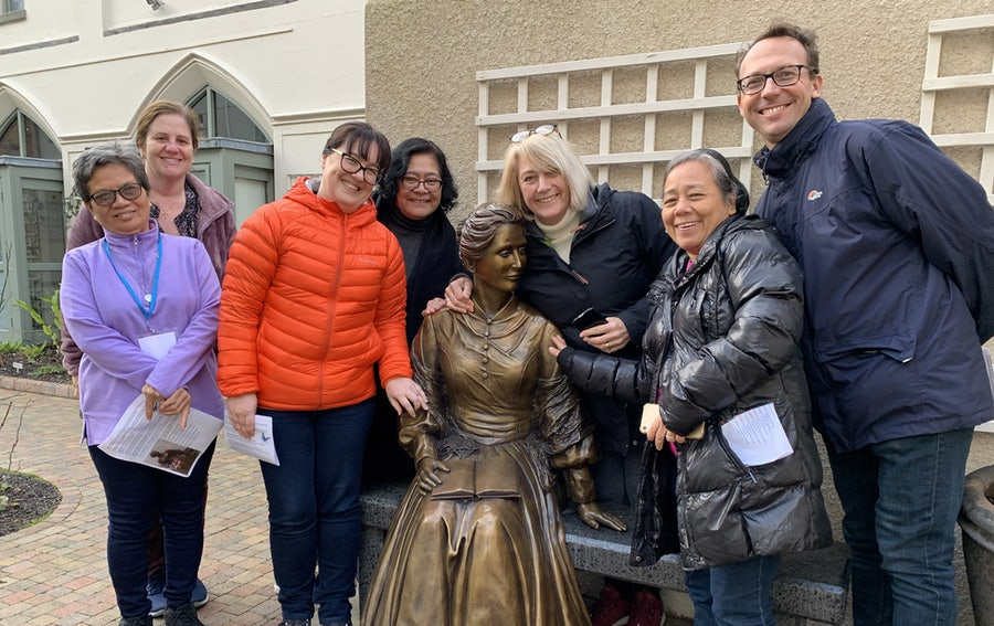 Some of the participants gathered at Catherine's statue in the Sacred Garden